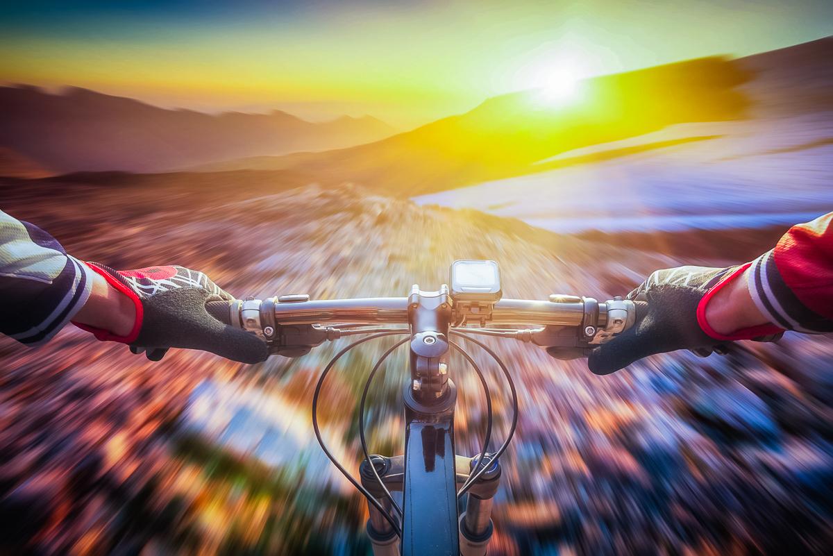 Biker speeding across the landscape at sunset